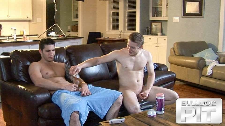 a straight jock holds his hard cock still while his friend dribbles lube over it