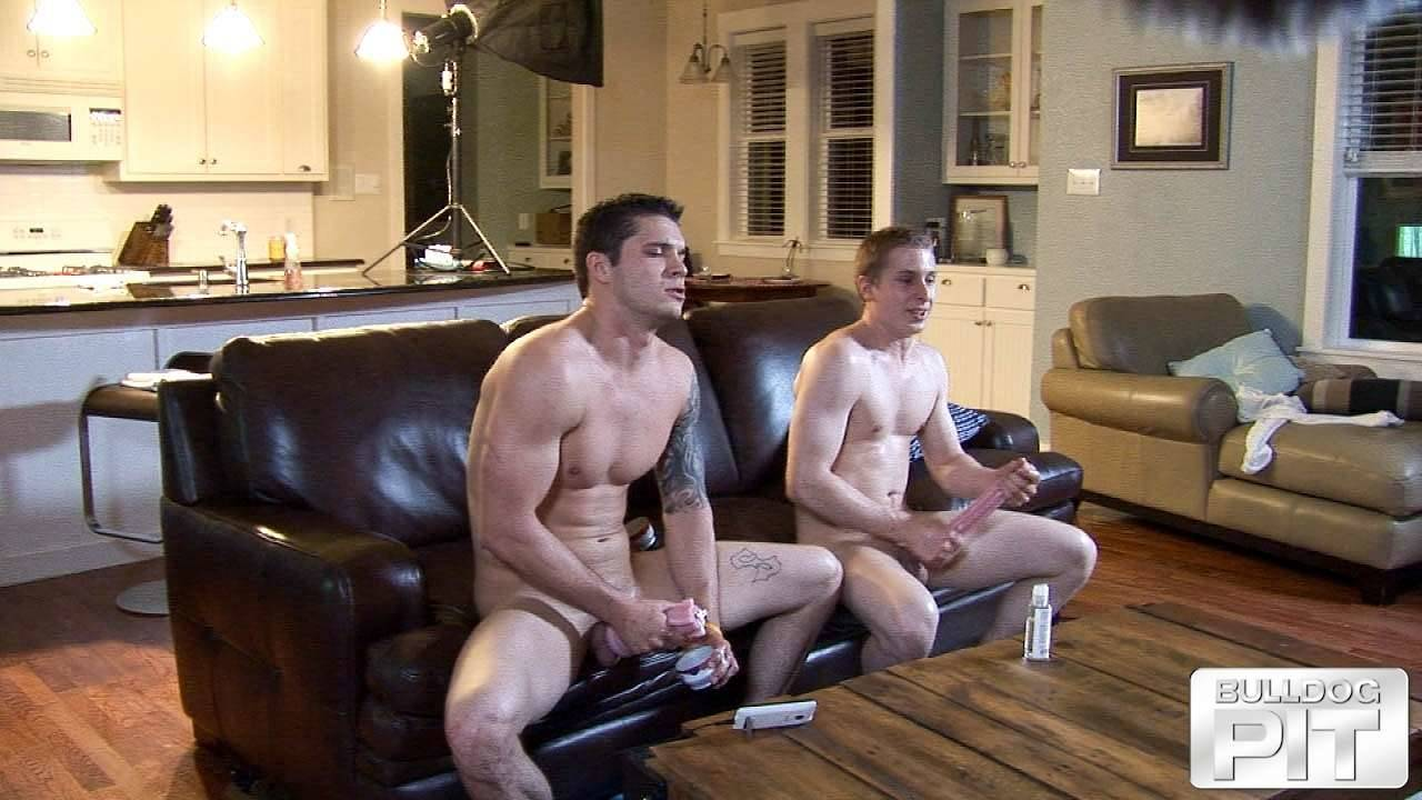 straight muscle jock leans forward on a couch and cums while his naked friend jerks off next to him
